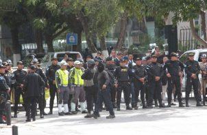 Jóvenes encapuchados son rodeados por miembros de la policía durante una protesta contra la investidura de Alejandro Giammattei FOTO/EFE