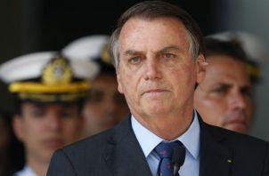 Pese a estar rodeado de escándalos, el presidente de Brasil, Jair Bolsonaro, ha logrado suprimir la disensión. Foto / Eraldo Peres/Associated Press.