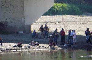 Migrantes de origen hondureño toman un descanso, este viernes, a la orilla del Río Suchiate. FOTO/AP