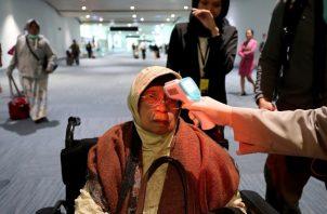 Un funcionario de salud escanea la temperatura corporal de un pasajero cuando llega al Aeropuerto Internacional Soekarno-Hatta en Tangerang, Indonesia. FOTO/AP