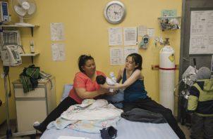Las mujeres inuit como Susie Mina (primera izq.) ahora pueden dar a luz cerca de casa. Con su hijo y Brenda Epoo, una partera. Foto / Amber Bracken para The New York Times.