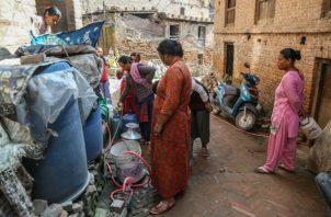 El agua de los camiones cisterna cuesta de 10 a 52 veces el agua de suministro público en 15 ciudades del mundo en desarrollo. Llenando envases. Foto / Purnima Shrestha para The New York Times.