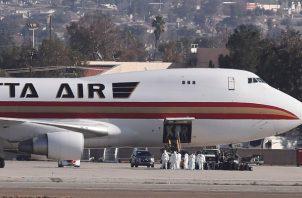 Las imágenes aéreas mostraron el avión proveniente de China estacionado en la mitad de la pista con la escalera extendida sin que los pasajeros descendieran inmediatamente. FOTO/AP