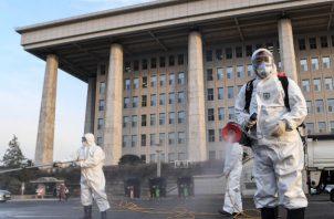 Trabajadores desinfectantes en aerosol en la Asamblea Nacional en Seúl, Corea del Sur, FOTO/AP