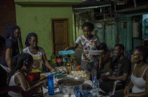 Migrantes de Camerún festejan un cumpleaños en un bar en Tapachula, México. Foto / Daniele Volpe para The New York Times.