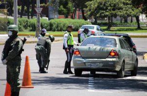 Agentes de la Policía Metropolitana de Quito y soldados del Ejército ecuatoriano controlan uno de los accesos a la ciudad para hacer cumplir las restricciones de circulación dentro del paquete de medidas para evitar la propagación del COVID-19. FOTO/EFE