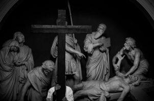 Un sacerdote porta una cruz en la procesión de la Estación de la Cruz, que precede las conmemoraciones del Viernes Santo, en París, Francia, limitadas por el confinamiento debido al Covid-19 Foto: EFE.