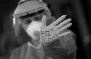 Trabajadora de salud, en un punto donde se realizan las pruebas rápidas del Covid-19 en Panamá, refuerza el mensaje: ¡Quédate en casa! Foto: EFE.