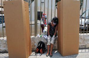Una mujer llora afuera de un cementerio en Guayaquil junto a cajas de cartón usadas como ataúdes. Foto / Jose Sanchez/Agence France-Presse — Getty Images.
