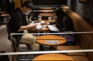 Un Starbucks en Hong Kong refuerza el distanciamiento social al no dar acceso a ciertas sillas y mesas. Foto / Jerome Favre/EPA, vía Shutterstock.