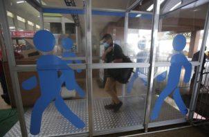 Usuarios de la terminal de transporte de Albrook pasan por una cabina de desinfección instalada en la terminal de autobuses antes de los abordajes.
