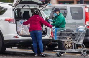 Los compradores cargan sus alimentos durante la pandemia de coronavirus COVID-19 en un Walmart. EFE
