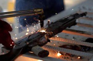 Un hombre corta un fusil con un soplete durante una destrucción de armas