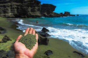 Mano con olivina molida en primer plano y al fondo una playa con arenas verdes. Project Vesta y Climitigation