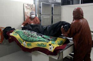 Un empleado de la morgue del Hospital Pampa de la Isla en Santa Cruz (Bolivia), prepara un cadáver. Fotos: EFE.