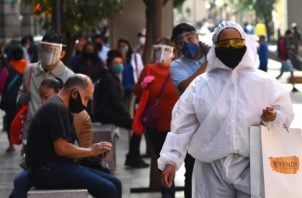 Un transeúnte viste un traje de alta seguridad sanitaria durante sus compras en el Centro histórico de Ciudad de México.