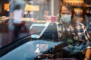 Un empleado de Whole Foods Market con cubrebocas durante la pandemia de coronavirus, frente a una caja registradora, en Washington. (Ting Shen/The New York Times)