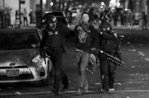 Un manifestante es detenido por la policía, luego de participar en una protesta contra el racismo y abuso policial en Portland, Oregon, Estados Unidos, este domingo 26. Foto: EFE.