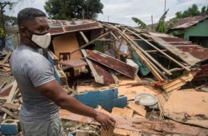 Un hombre intenta reparar su vivienda dañada por el paso del huracán Isaías. FOTO/EFE