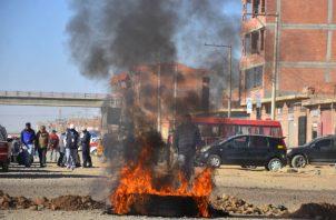 Un hombre cruza un bloqueo de una carretera durante las protestas en Cochabamba. Fotos: EFE.BOL12. COCHABAMBA (BOLIVIA), 03/08/2020.- Un grupo de personas bloquea una carretera durante una protesta por el nuevo aplazamiento de las elecciones bolivianas este lunes, en Cochabamba (Bolivia). Bolivia vive este lunes una jornada con bloqueos y manifestaciones de sectores sociales que exigen que las elecciones sean el 6 de septiembre y no el 18 de octubre como anunció el organismo electoral del país. EFE/ Jorge Á