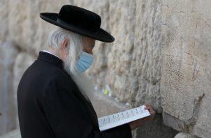 Judíos ortodoxos oran en el muro al oeste de la vieja ciudad de Jerusalén, a dos días de reiniciar el aislamiento total por el coronavirus. EFE.