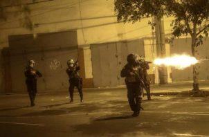 """Según revelan vdeos de la marcha, """"agentes que formaban una barrera dispararon municiones no identificadas en cuatro ocasiones, mientras uno de ellos gritaba 'Mátalo, mátalo'"""". Foto: EFE"""