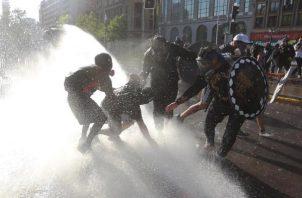 Manifestantes enfrentan a los carabineros durante una nueva jornada de protestas antigubernamentales. EFE