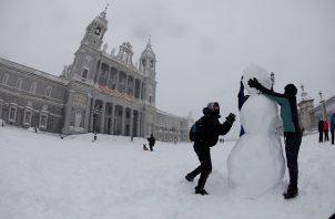 Personas hacen hoy un muñeco de nieve en las inmediaciones de la Catedral de la Almudena , en Madrid. Foto: EFE