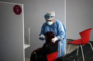 Personal sanitario realiza una prueba de coronavirus a una viajera en Buenos Aires (Argentina). EFE
