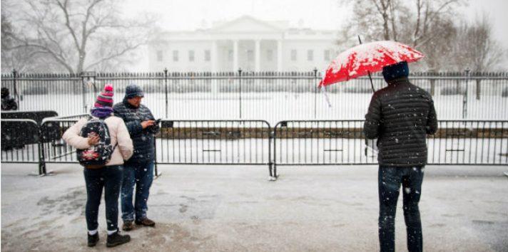 Varias personas contemplan el exterior nevado de la Casa Blanca en Washington D.C (Estados Unidos), durante la tormenta de nieve. Foto: EFE