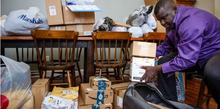 Aly Thioye se volvió mensajero para pagar visitas a Senegal. Prepara paquetes en su hogar en Rhode Island. Foto / Monica Jorge para The New York Times.