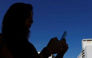 Una mujer mira su teléfono móvil.