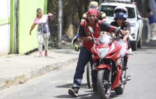 Los saqueadores se van con una motocicleta que acaban de sacar de una tienda en Managua. AP