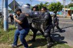 Los agentes, cubiertos con su armadura de protección, salieron en fila de la sede de la Policía Nacional cargando sus porras y escudos antidisturbios que utilizaron para dispersar a los comunicadores.
